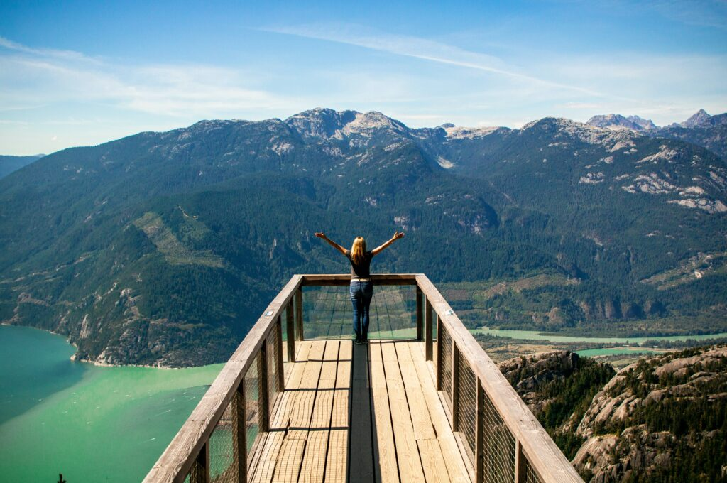 woman looking out across mountains with her hands raised up